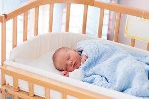 Baby im Beistellbett im Elternschlafzimmer kann vor plötzlichen Kindstod schützen