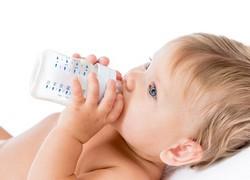 Mädchen trinkt aus Babyflasche