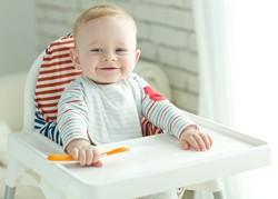Baby wartet im Hochstuhl auf Essen