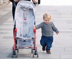 Kleinkind geht neben dem Buggy
