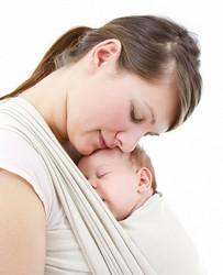 Baby kuschelt bei Entwicklungsphasen in einem Tragetuch mit Mama